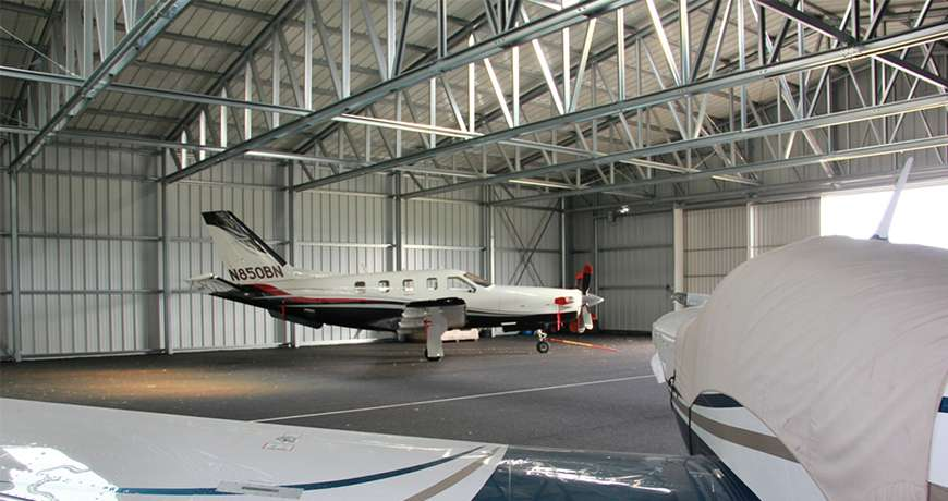 White and blue business jet parked inside a steel dry and safe metal building.