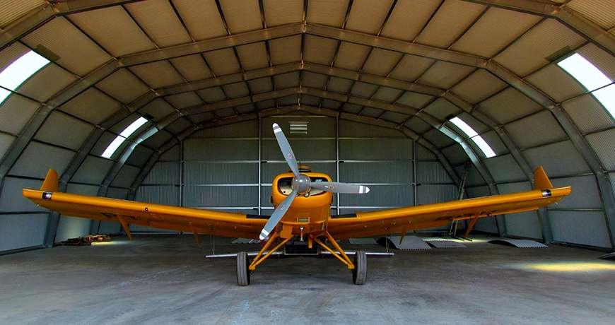 Orange airplane sheltered in a semicircle steel metal hangar